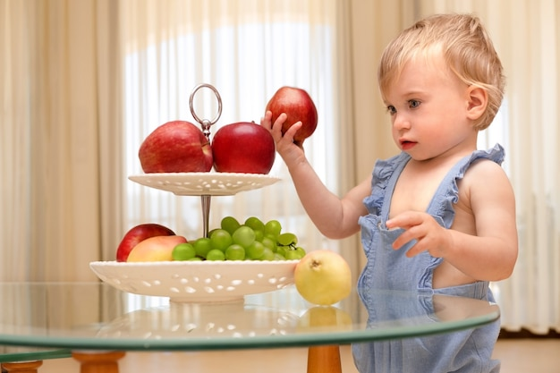 Милая кавказская белокурая девочка 12 лет держит красное яблоко и смотрит на миску со свежими фруктами