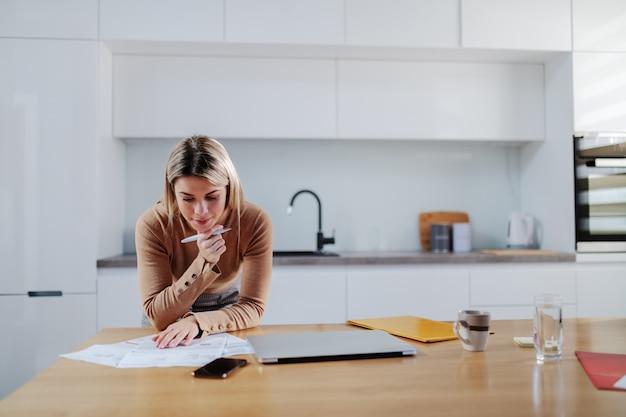 Милая кавказская белокурая женщина в свитере, опираясь на обеденный стол и подсчитывая счета. в руке ручка. интерьер квартиры.
