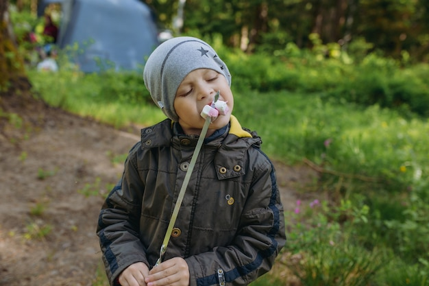 Cute caucasian boy eating roasted marshmallow strung on skewer