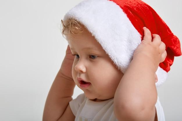 白いスペースに対してサンタの帽子をかぶっているかわいい白人の男の子、目をそらしているブロンドの髪の幼児、白いtシャツを着ています