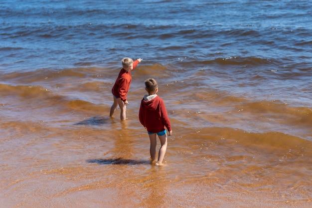 ラドガ湖の波から走っている赤いパーカーと青いパンツを着ているかわいい白人の男の子