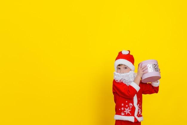 산타클로스 옷을 입고 수염을 기른 귀여운 백인 소년이 분홍색 둥근 선물 상자를 올렸다