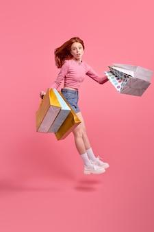 かわいい白人女性のカジュアルな服は、手に購入したパッケージを持って、買い物の後に急いでいます。人々のライフスタイルの概念。コピースペースをモックアップします。スタジオで孤立したピンクの背景