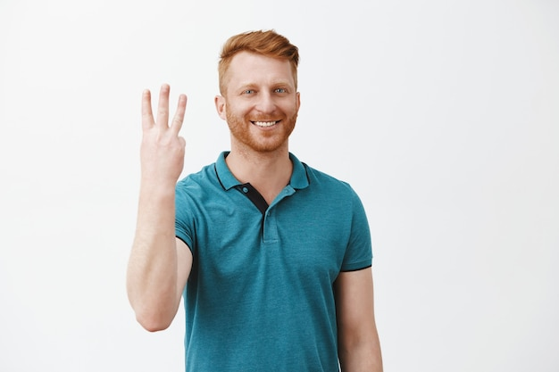 Cute caucasian friendly redhead man ordering three shots from bartender, smiling broadly showing number third and smiling broadly