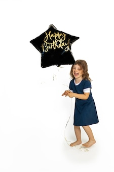 Cute caucasian girl child 4-5 years old playing merrily happy with black gel balloon with the inscription happy birthday. photo in studio against a white background