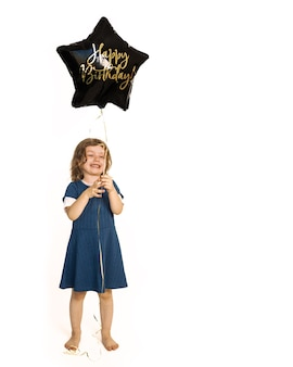 Cute caucasian girl child 4-5 years old spoiling merrily happy play with black star-shaped gel balloon with inscription happy birthday. photo in studio against white background.