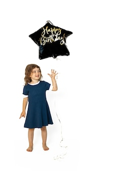 Cute caucasian girl child 4-5 years old spoiling merrily happy with black star-shaped gel balloon with inscription happy birthday. photo in studio against a white background