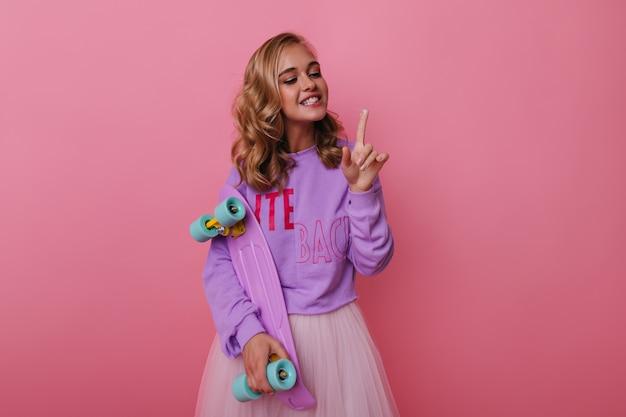スケートボードでポートレート撮影中に身も凍るようなかわいい白人の女の子。ロングボードを保持している紫色の衣装で見事な女性モデル。