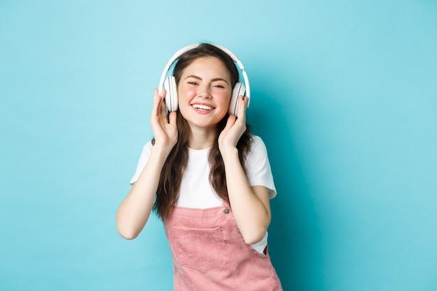 Симпатичная кавказская девушка в весеннем наряде, слушая музыку в наушниках, довольная улыбка в камеру, стоя на синем фоне.
