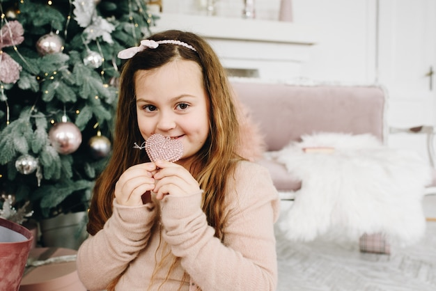 Cute caucasian girl sitting near christmas tree holding a heart-shaped decoration