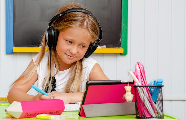 かわいい白人の女の子は笑顔で自宅教育でタブレットを見てします。