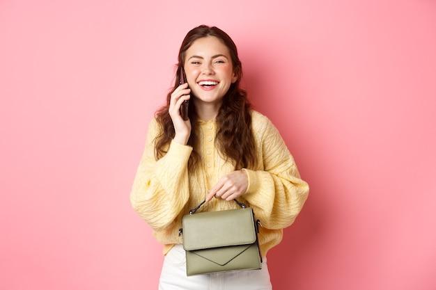 Милая кавказская девушка разговаривает по телефону и смеется, держа кошелек, улыбаясь счастливой в камеру, стоящую у розовой стены