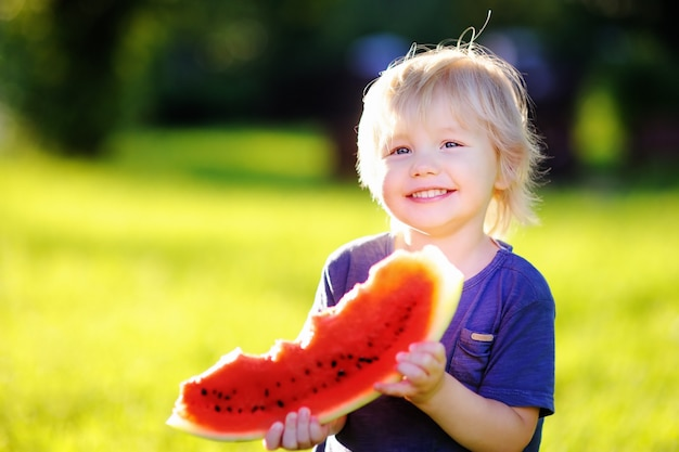 Cute caucasian little boy with blond hairs eating fresh watermelon outdoors