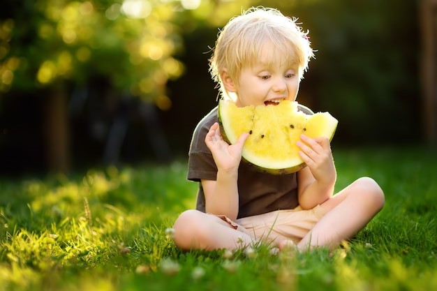 Cute caucasian little boy with blond hairs eating yellow watermelon outdoors