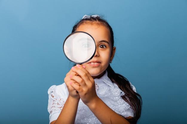 青い背景に虫眼鏡で遊んでいるかわいい白人の少女。