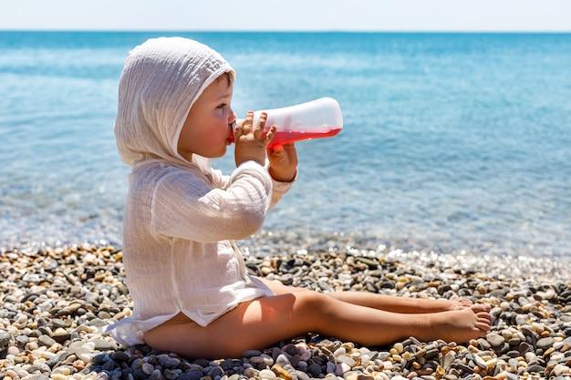 Симпатичный кавказский маленький ребенок ясельного возраста сидит на пляже и любит пить детскую морс у моря на пляже летом.
