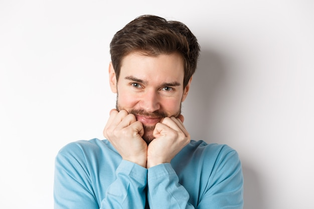 Cute caucasian man looking at something with admiration and desire, touching face with silly smile, standing over white background.