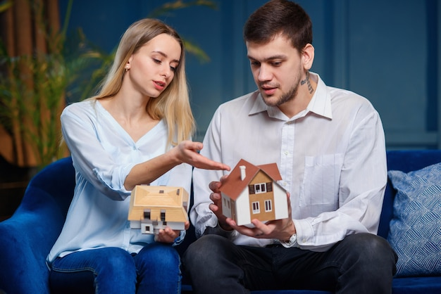Cute caucasian man and woman discussing two model of 3d maket of house.