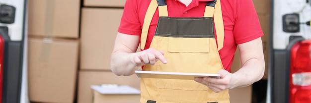 Симпатичный кавказский почтальон в костюме и кепке проверяет почтовые ящики с планшетным устройством в руках