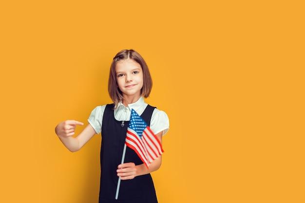 손과 손가락으로 미국 국기를 가리키는 미국 국기를 들고 있는 귀여운 백인 여학생