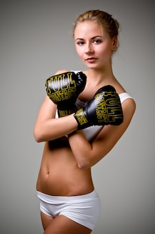 Cute caucasian slim girl boxer in white lingerie posing on a gray background in the studio. strong sports woman concept. places for advertising