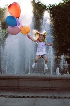 噴水からジャンプする風船を保持しているカラフルな染めた髪のかわいい白人の笑顔の女の子