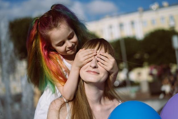 バルを保持している彼女の目を閉じているお母さんの後ろに立っているカラフルな染めた髪を持つかわいい白人の笑顔の女の子
