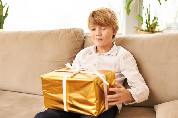 彼の膝の上に新年の贈り物を持ってソファに座っているかわいい白人のティーンエイジャー。クリスマスプレゼントが入った金色の箱を開ける準備ができているハンサムな男の子、好奇心旺盛な予想される表情を持って、笑顔
