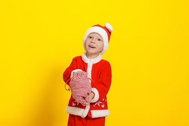 산타클로스 옷을 입은 귀여운 백인 3세 소년이 새해를 맞아 손을 자루에 넣었다
