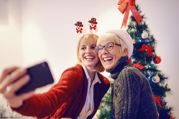 Cute caucasian woman and her mother taking selfie in front of decorated christmas tree. christmas time.