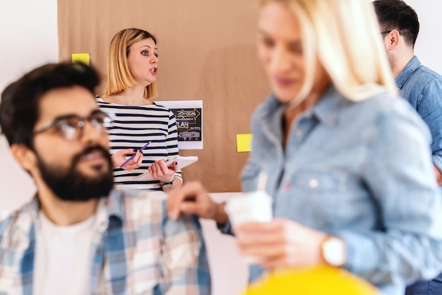 Cute caucasian woman talking about object with colleague and standing in front of paper with business plan pasted to wall. blurred foreground. start up business concept.