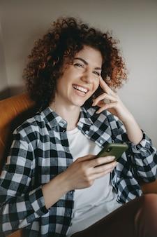 Милая кавказская женщина с вьющимися волосами улыбается, сидя на диване и болтая по мобильному телефону