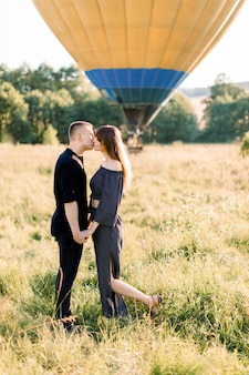 Cute caucasian young couple in love, standing in summer field, holding hands and kissing. hot colorful air balloon at sunrise