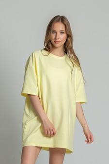 白い背景の上の黄色のtシャツでポーズをとってかわいい白人の若い女性