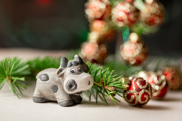 Cute ceramic bull as symbol of new year 2021 next to fir branch and christmas tree