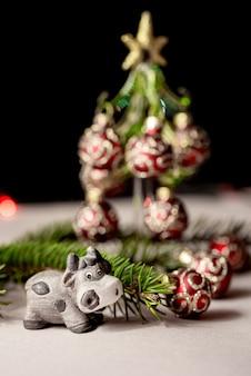 モミの枝とクリスマスツリーの横にある新年2021年のシンボルとしてかわいいセラミック牛