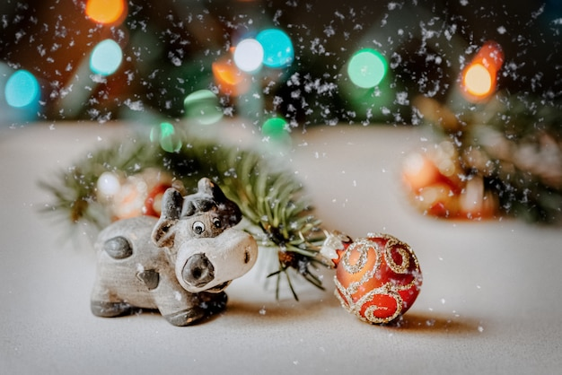 赤いボールで飾られたクリスマスツリーの枝の横にある背景のぼけボケ味の新年2021年のシンボルのようなかわいいセラミック牛