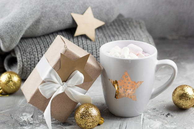 Cute ceramic cup, gift box and knitted sweaters on a gray shabby background