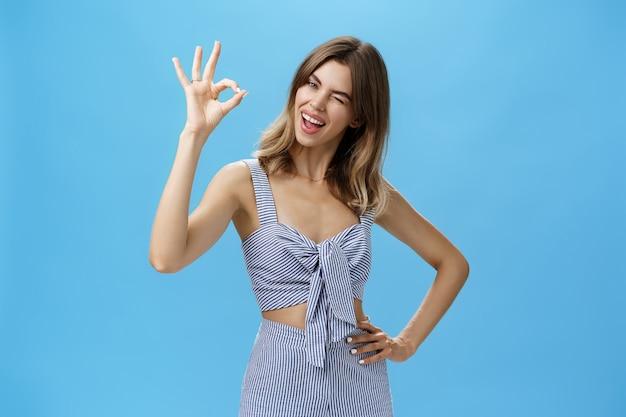 틈이 있는 이빨을 가진 귀여운 카리스마 넘치는 여성이 와이셔츠에 즐겁게 손을 잡고 머리를 기울이는 괜찮은 제스처를 보여줍니다...
