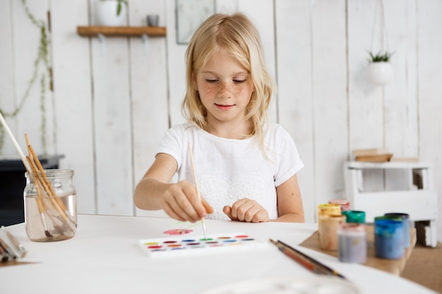 Cute and charming blonde girl wearing white t'shirt deeping brush into paint