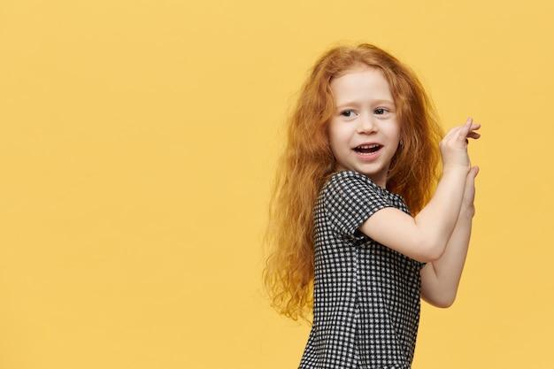 Bambina europea affascinante carina in vestito elegante che balla alla musica, sentendosi libera