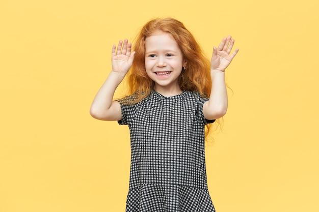 Милая очаровательная европейская маленькая девочка в элегантном платье танцует под музыку, чувствуя себя свободно