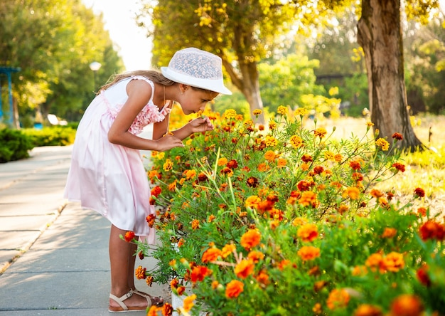 A cute charming girl in a beautiful pink dress sniffs fiery marigolds in a bright park on a sunny day on a long awaited vacation