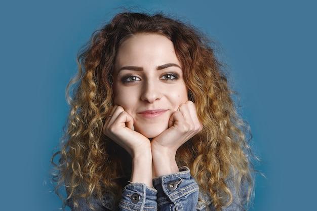 Carina affascinante ragazza ventenne che riposa il mento sulle sue mani con interesse mentre ascolta una bella storia. giovane femmina allegra sorridente in denim che posa alla parete blu