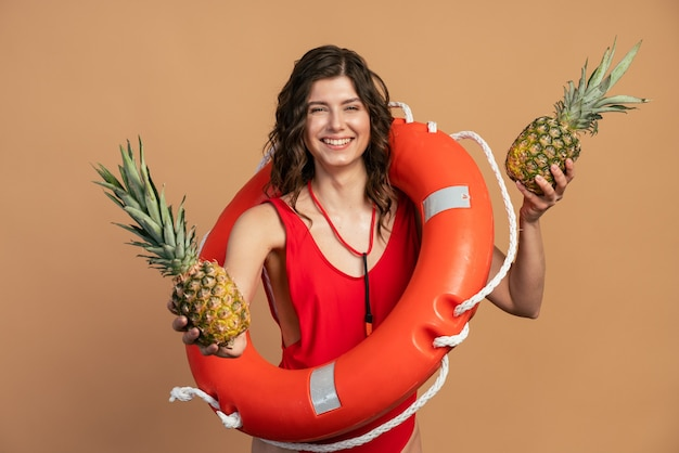 パイナップルを持って首に救命浮環を持ったキュートでチャーミングな女の子。オレンジ色の背景に赤い水着の若い女性