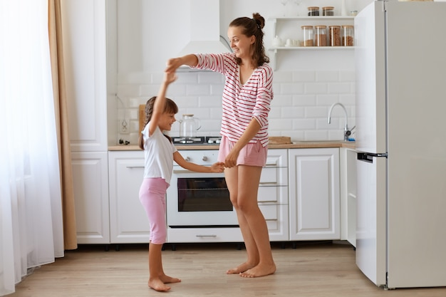 Cute charming little girl dancing with mother, r feeling amazing dancing with her loving mommy, expressing happiness and positive emotions, family having fun at home.