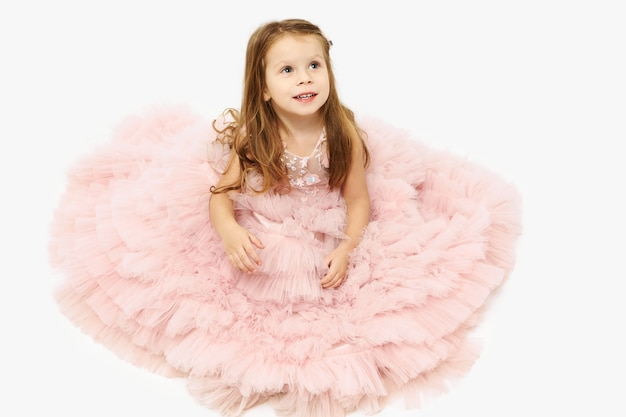 Cute charming little girl with loose straight hair sitting on floor with ballet skirt covering her legs and feet