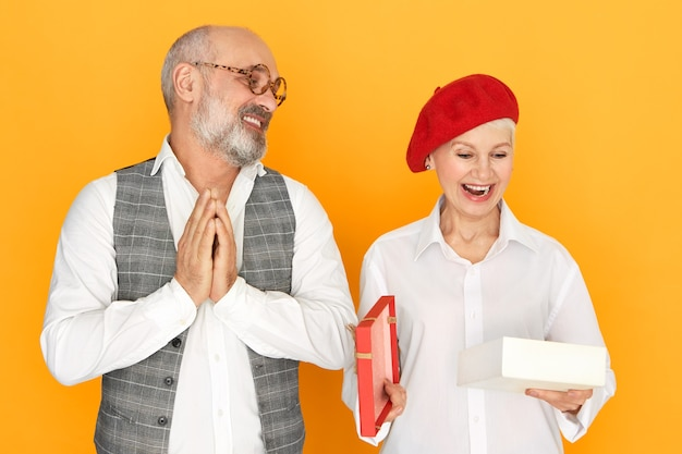 Cute charming middle aged female in stylish headwear opening mouth in excitement while opening box with present from her husband on birthday, bearded senior man rubbing hands with pleasure