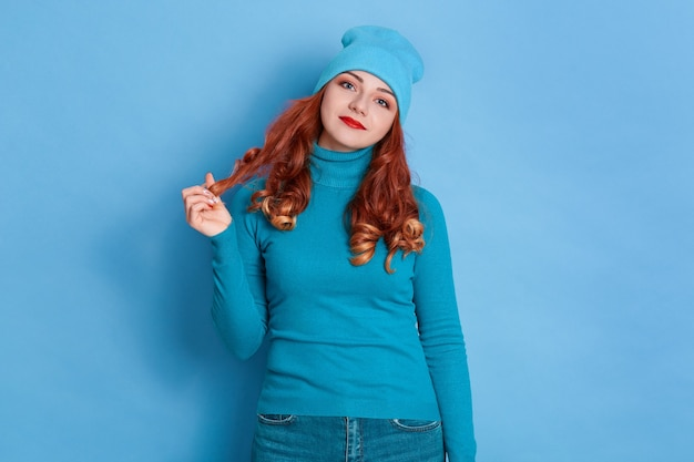 Cute charming woman with red hair dresses sweater and cap