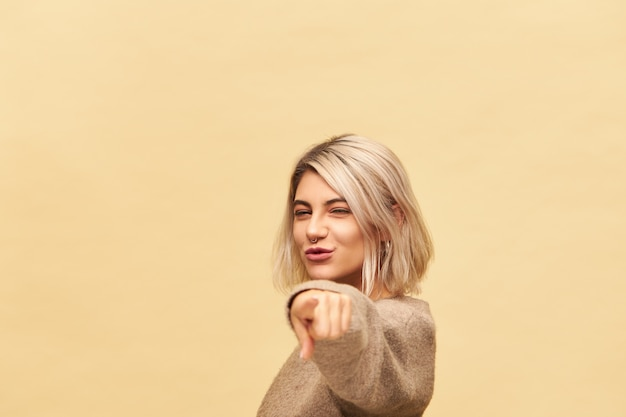 Cute charming young blonde woman in cashmere sweater reaching out hand and pointing index finer, choosing you, inviting to dance with her, having energetic enthusiastic look, smiling